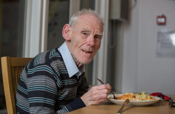 Elderly man eating a meal